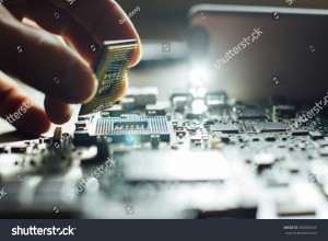 stock-photo-technician-plug-in-cpu-microprocessor-to-motherboard-socket-workshop-background-350350565